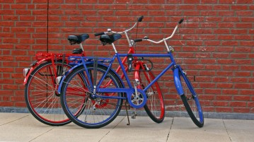 Red and blue bikes in front of a wall of bricks.